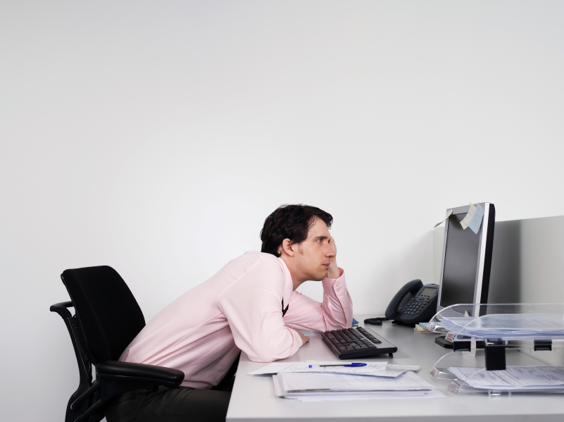 Bored Male Office Worker At Desk - Health Risks faced by office workers in Malaysia